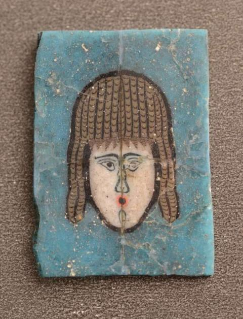 An egyptian mosaic glass inlay of a new comedy theatre mask.